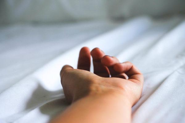 Geoeffnete Hand mit trockener Haut auf weissem Laken.