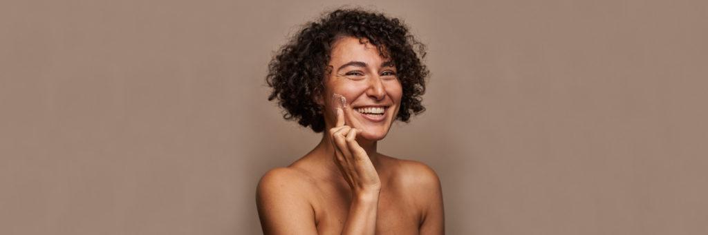 Lachende Frau cremt ihr Gesicht ein.