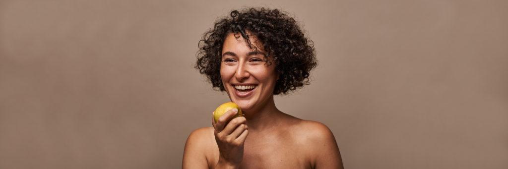 Lachende Frau beisst in Apfel.