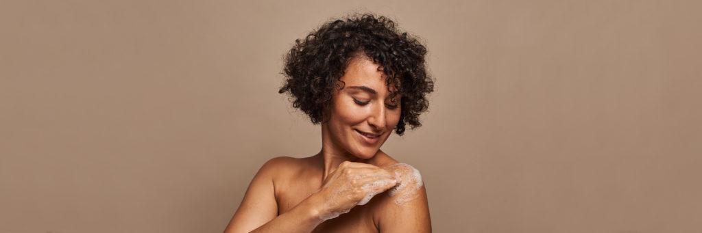 Laechelnde Frau reinigt Haut mit Seifenschaum.