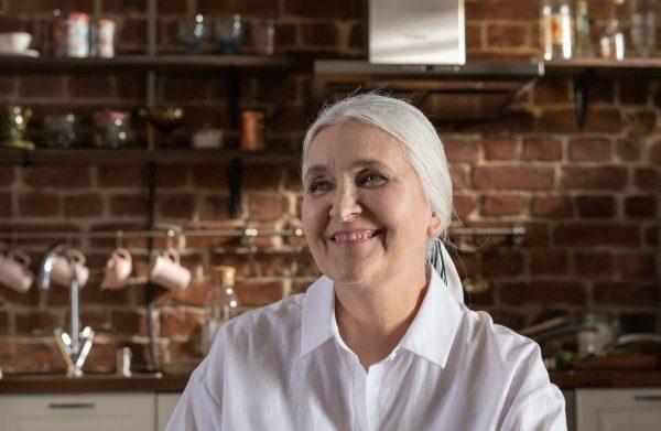 laechelnde Frau mit grauen Haaren lebt nach Slow Aging