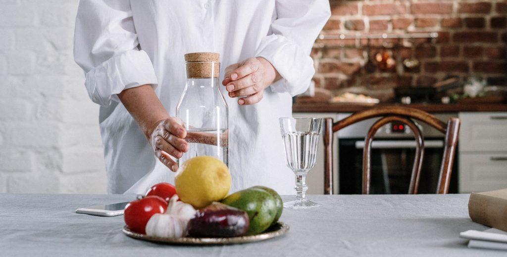 Frau in weisser Bluse greift nach Wasserflasche und Obst